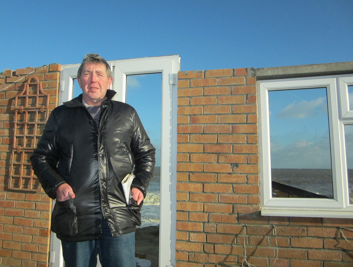 Steven Connolly by his bungalow in Hemsby, Norfolk, which fell into the sea last night as the tidal surge caused the cliff to