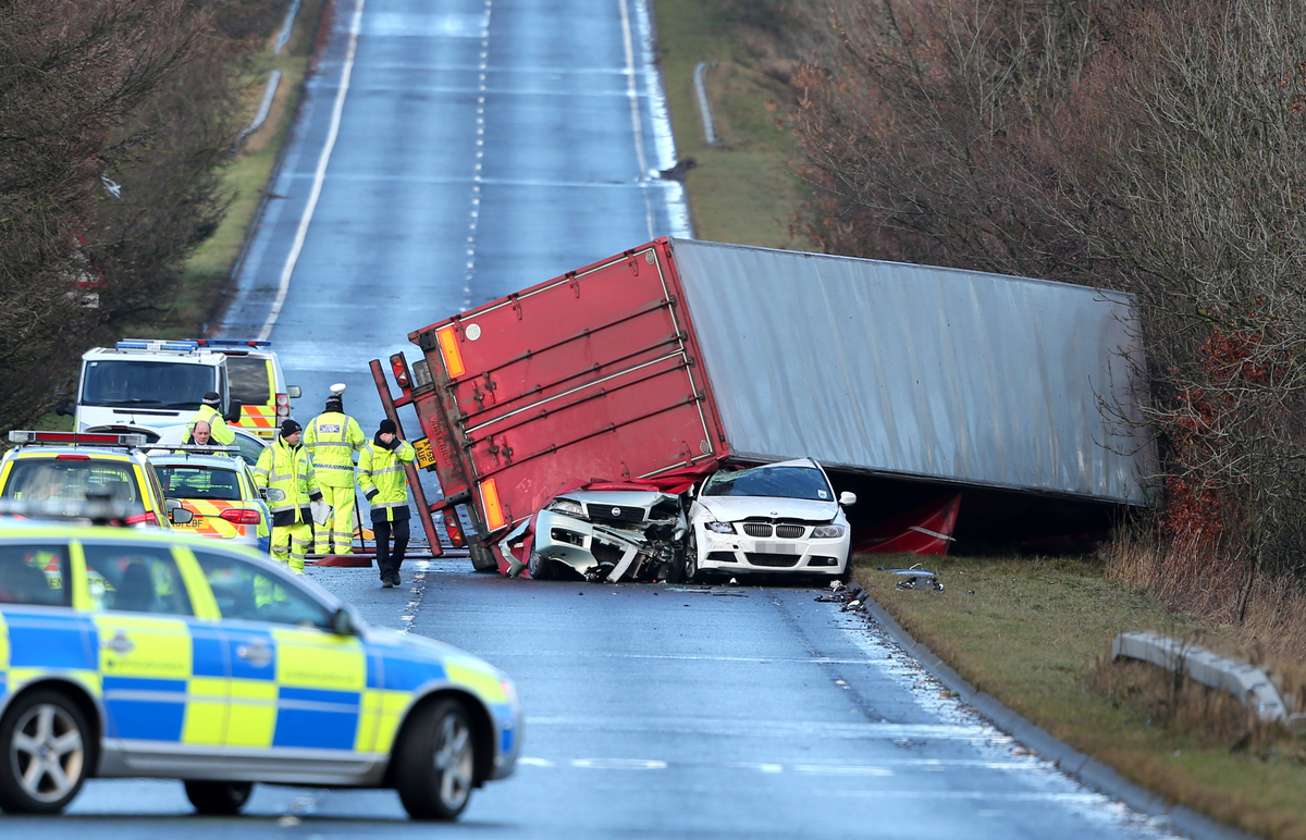 Police at the scene where a lorry driver died as his HGV toppled on to a number of cars on the A801 in West Lothian as the ga