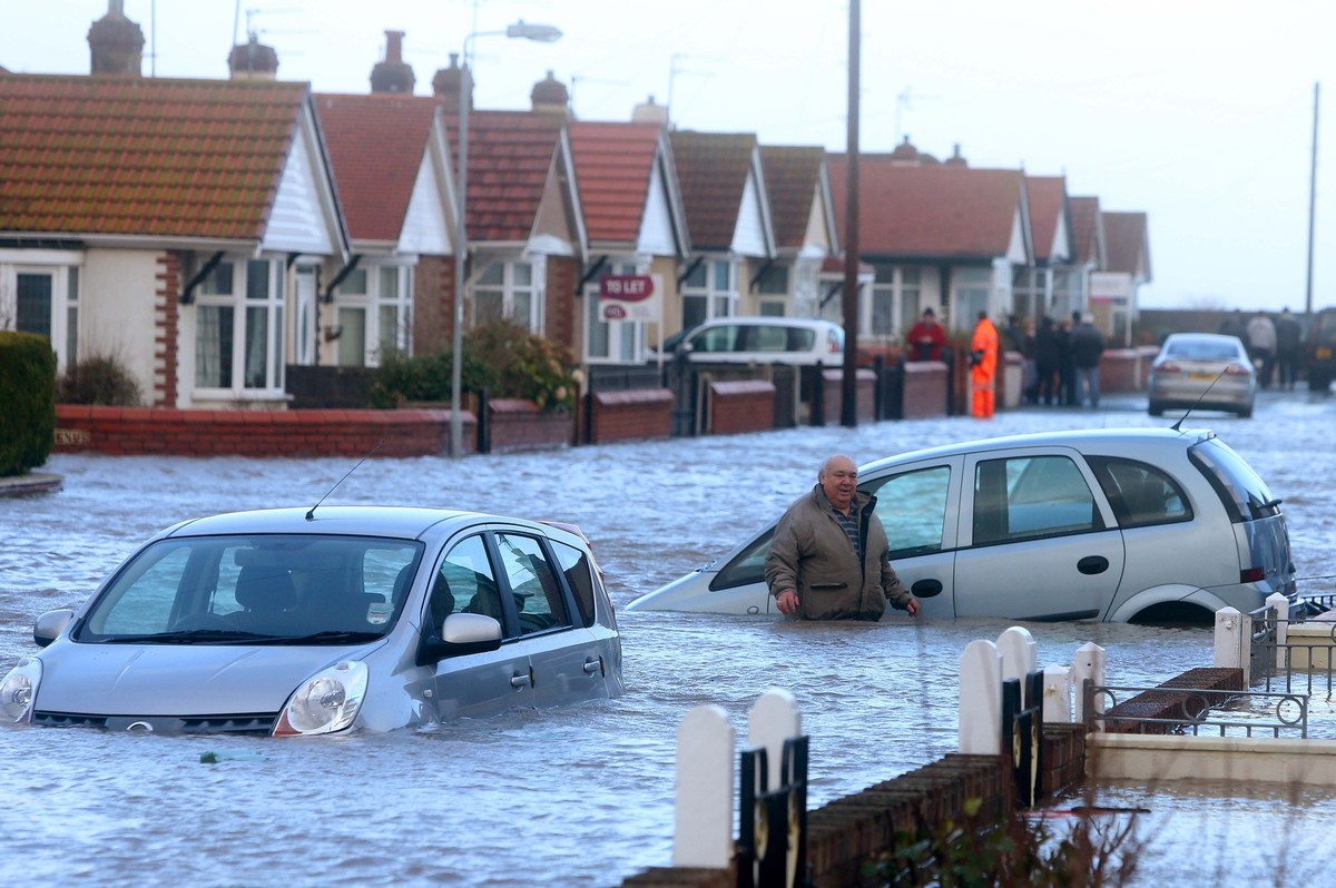 A man walks through the floods in Rhyl as heavy seas and high tides sweep across the country.