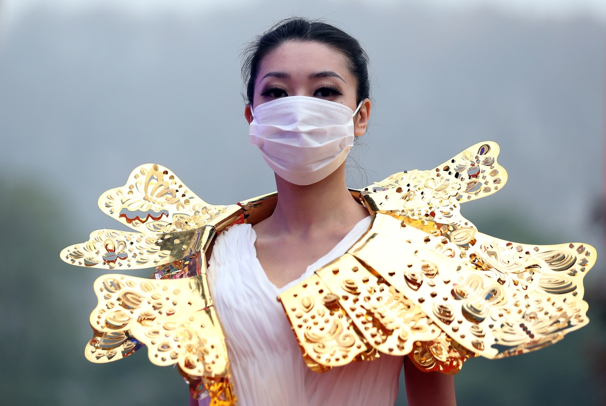 This picture taken on December 7, 2013 shows a model wearing a surgical mask as she parades a collection of gold jewelleries
