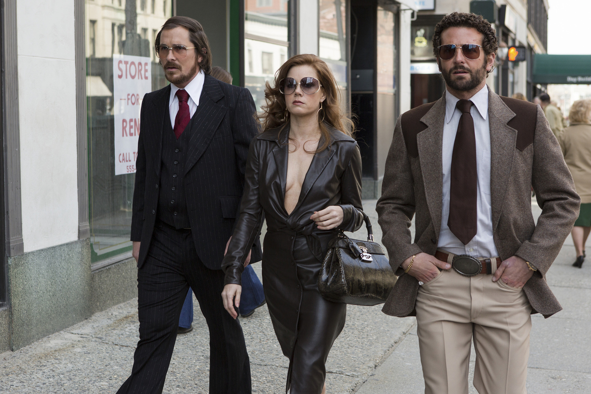 This photo released by Sony Pictures shows Christian Bale, left, as Irving Rosenfeld, Amy Adams as Sydney Prosser, and Bradle