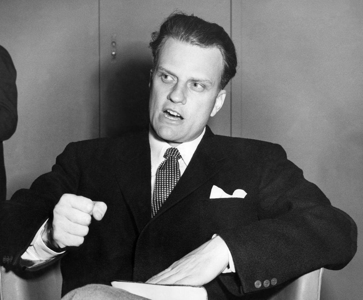 SOUTHAMPTON, UNITED KINGDOM:  Billy Graham, the American evangelist, the Bible beneath his hand, pounds his knee as he is int