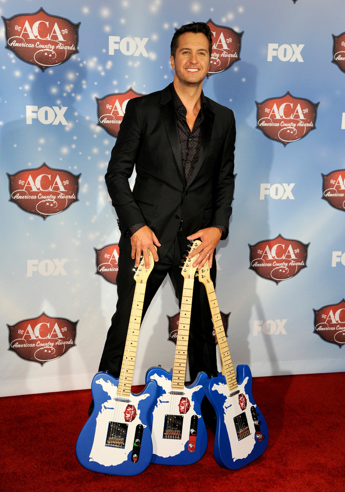 Luke Bryan poses backstage with the awards for artist of the year, artist of the year: male, and touring artist of the year,