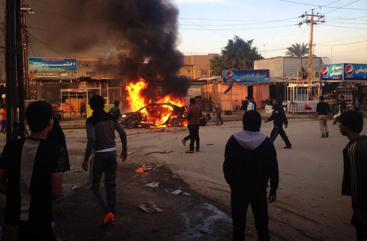 <em>Caption: Iraqis gather around a burning car at the scene of an explosion in the Shiite Muslim Al-Amin district of Baghdad