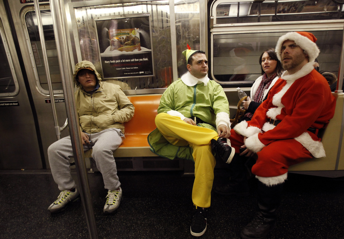 FILE - This Dec. 11, 2010 file photo shows John Paul, center, of Manhattan, dressed as an Elf and Michael Smallwood, of Brook
