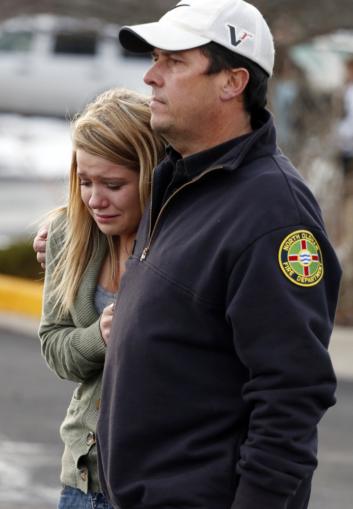 A father picks up his daughter at a church where students from nearby Arapahoe High School were evacuated to after a shooting
