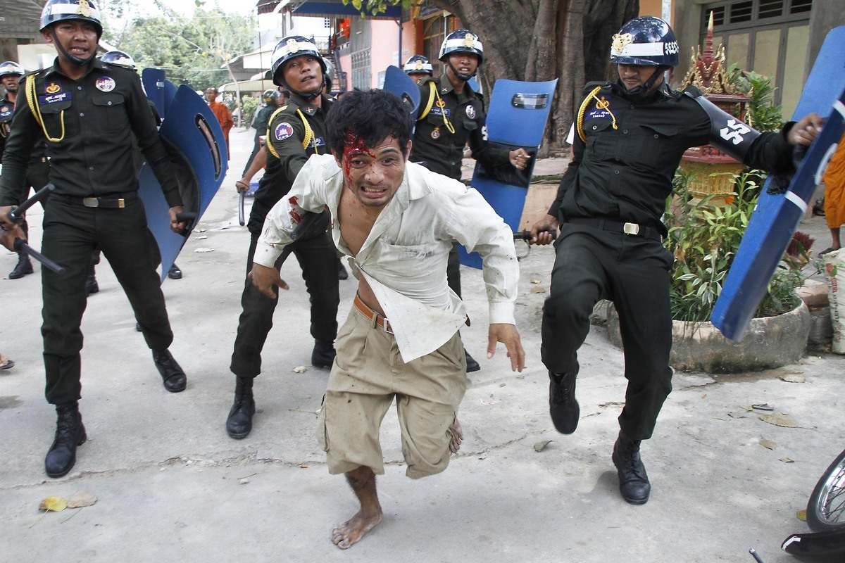 An injured Cambodian worker escapes from riot police in the compound of a Buddhist pagoda in Phnom Penh, Cambodia, Tuesday, N