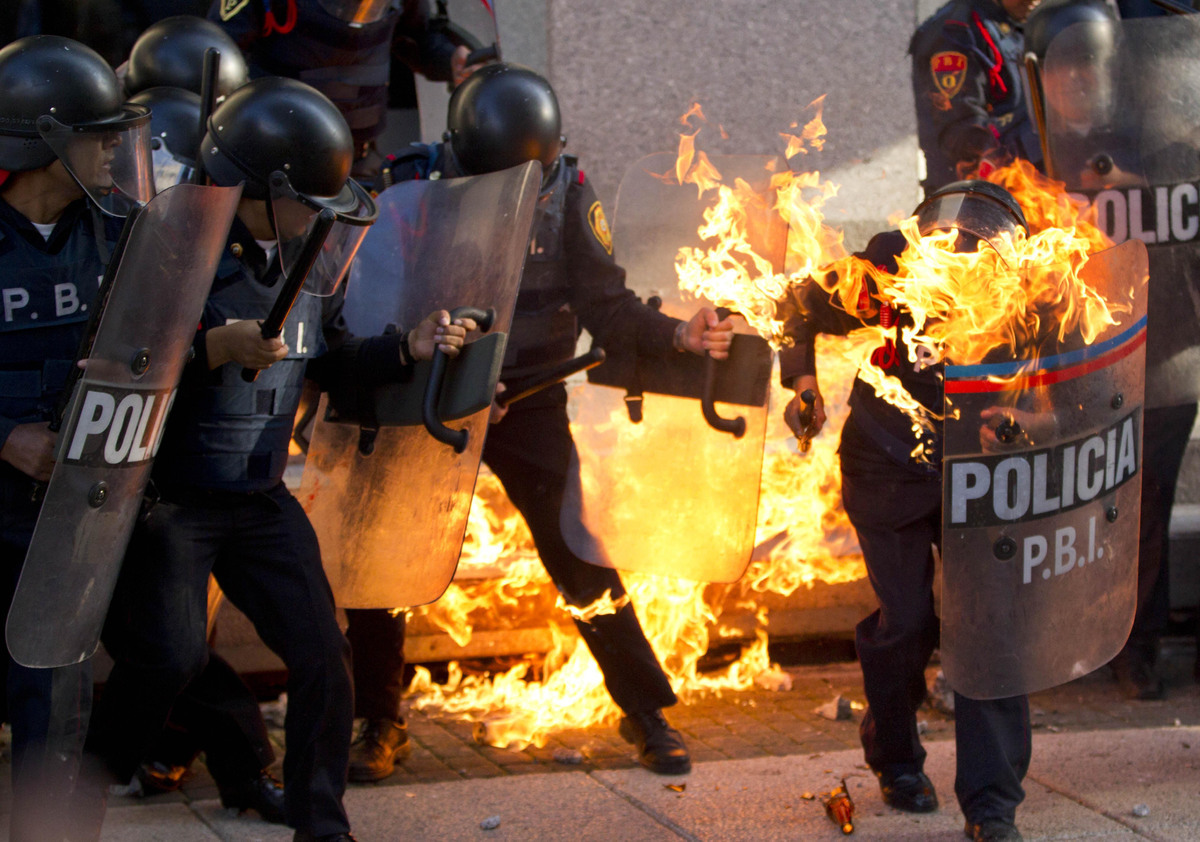 A police officer is engulfed in flames after being hit by a Molotov cocktail thrown by protesters marking the anniversary of