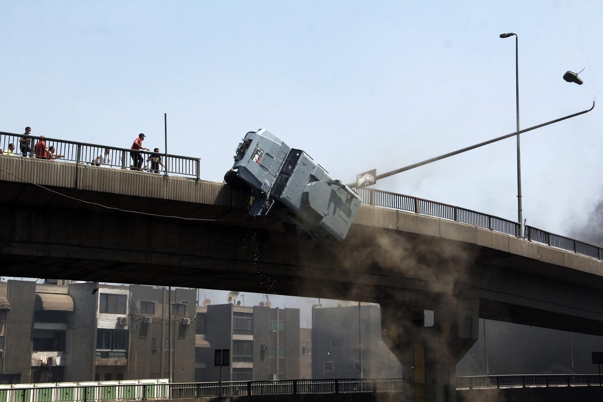 A police vehicle falls off of the 6th of October bridge close to the largest sit-in by supporters of ousted Islamist Presiden