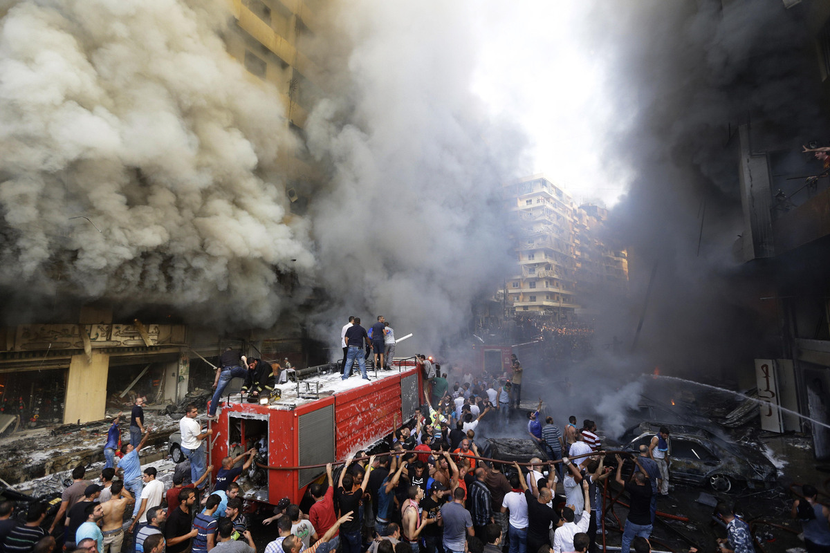 Lebanese citizens and Hezbollah supporters gather at the scene of a car bomb explosion in southern Beirut, Lebanon, Thursday