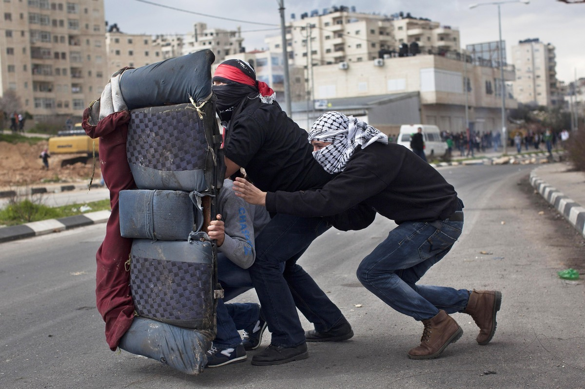 Masked Palestinians use a back car seat as a shield during a protest in support of Palestinian prisoners, outside an Israeli