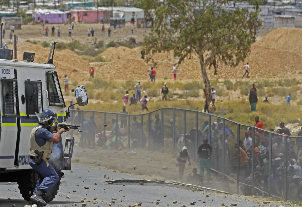 A South African policeman, left,  fires a rubber bullet at striking farm workers as they demonstrate in De Doorns, South Afri