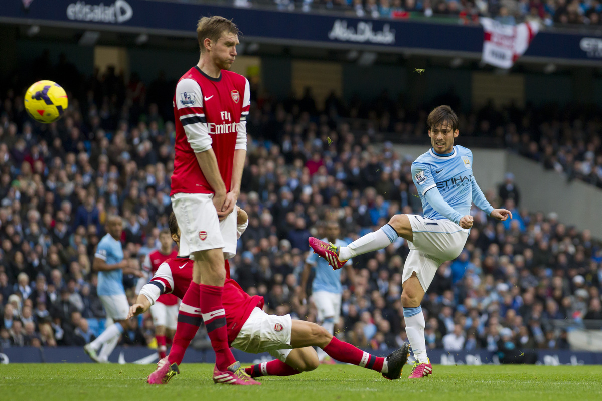 Manchester City's David Silva, right, has a shot at goal during his team's English Premier League soccer match against Arsena