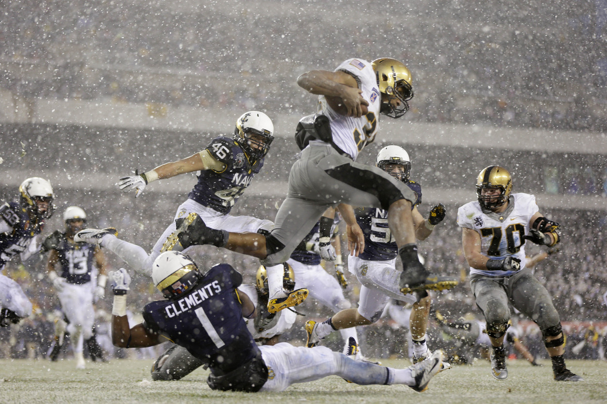 Army running back Terry Baggett (31) jumps over defender Navy cornerback Brendon Clements (1) during the first half of an NCA