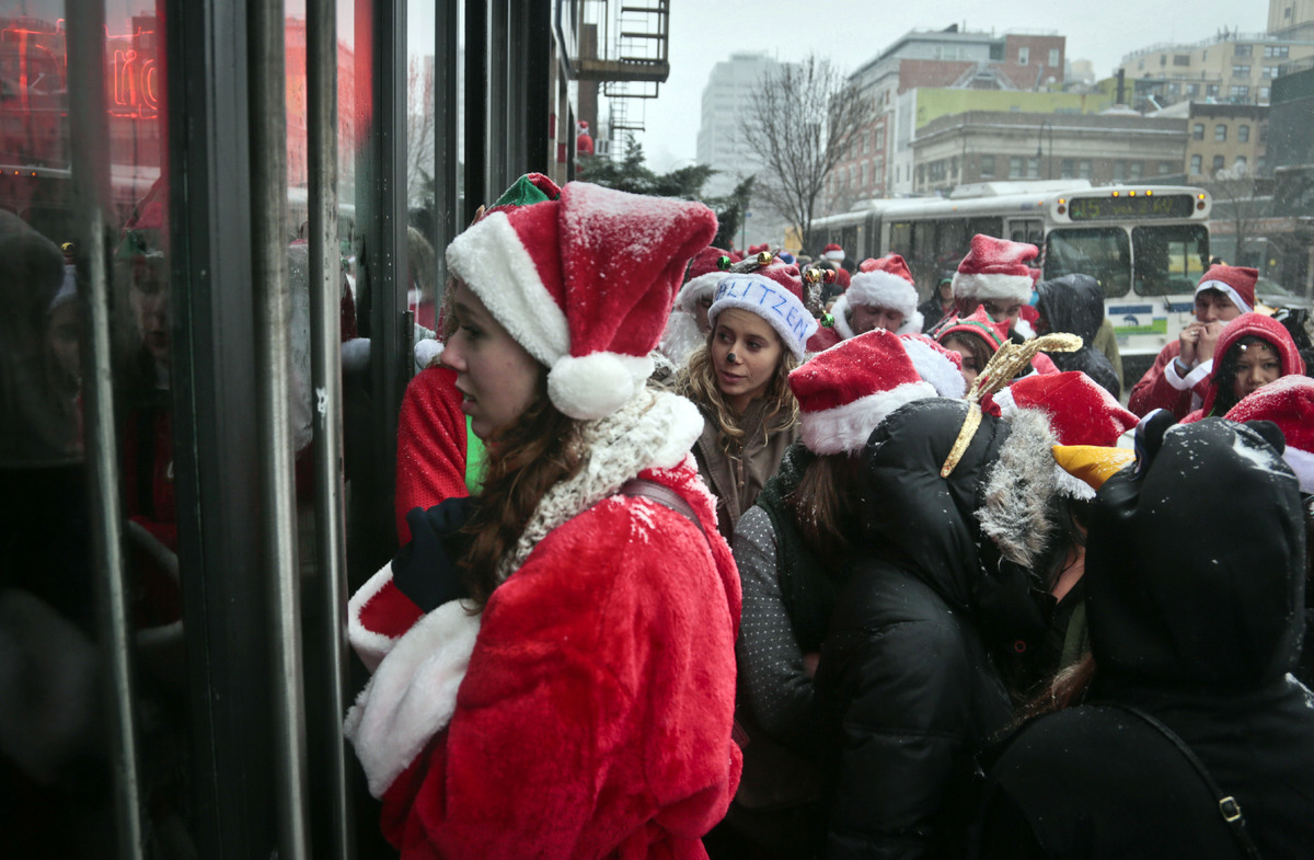 Santacon participants wait outside a lower eastside bar filled to capacity on Saturday, Dec. 14, 2013 in New York. Thousands