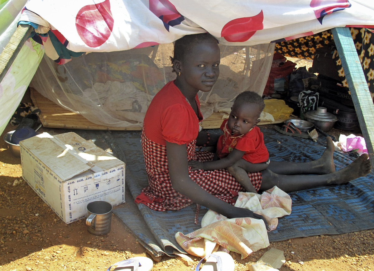 In this photo taken Monday, Dec. 23, 2013 and released by the World Food Programme (WFP), a woman and child sit in the shade