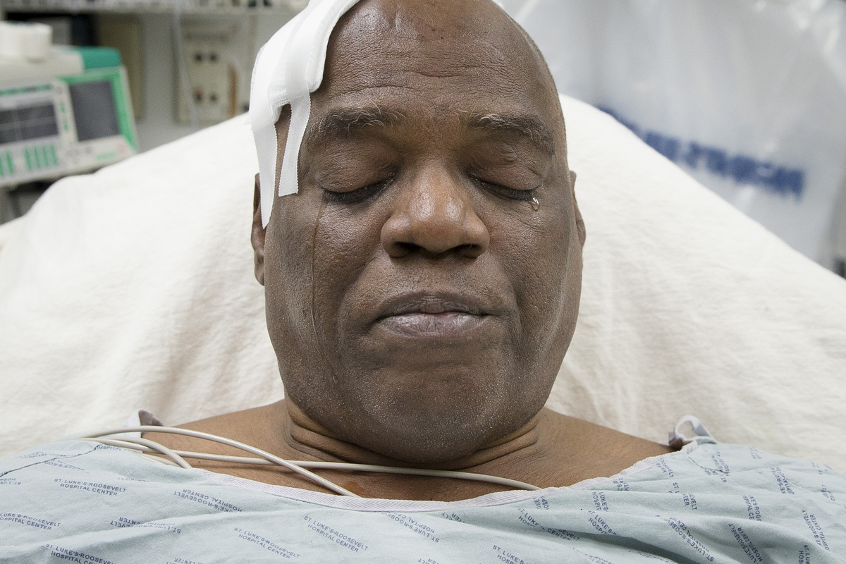 Cecil Williams cries during an interview as he rests in his hospital bed following a fall onto subway tracks from the platfor