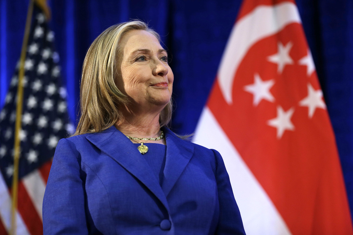 U. S. Secretary of State Hillary Rodham Clinton waits to speak as she is introduced at Singapore Management University, Satur