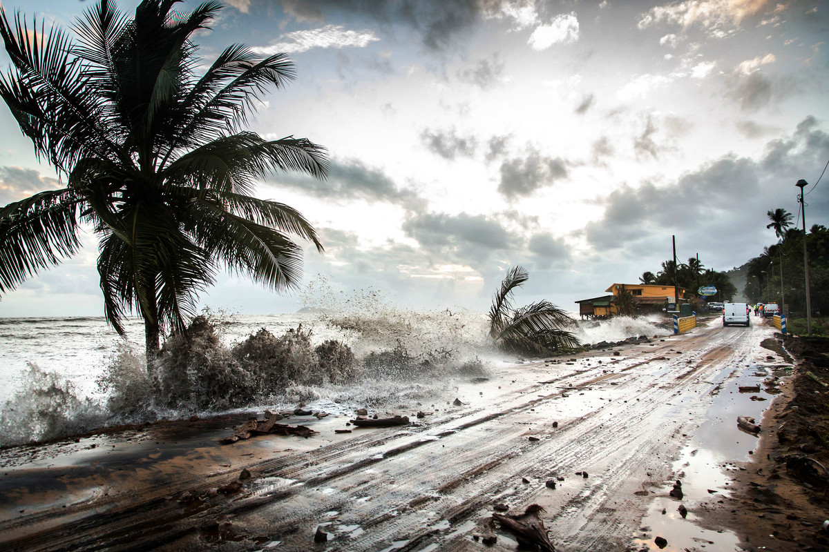 """Waves hit the road along the sea near Cayenne on January 15, 2013. The coast of Guyana switched to """"red alert"""" today as sever"""