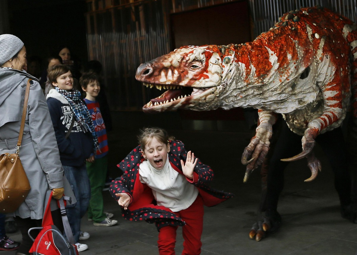 Children react as a carnivorous theropod known as the Australovenator dinosaur walks through crowds along the Southbank, in L