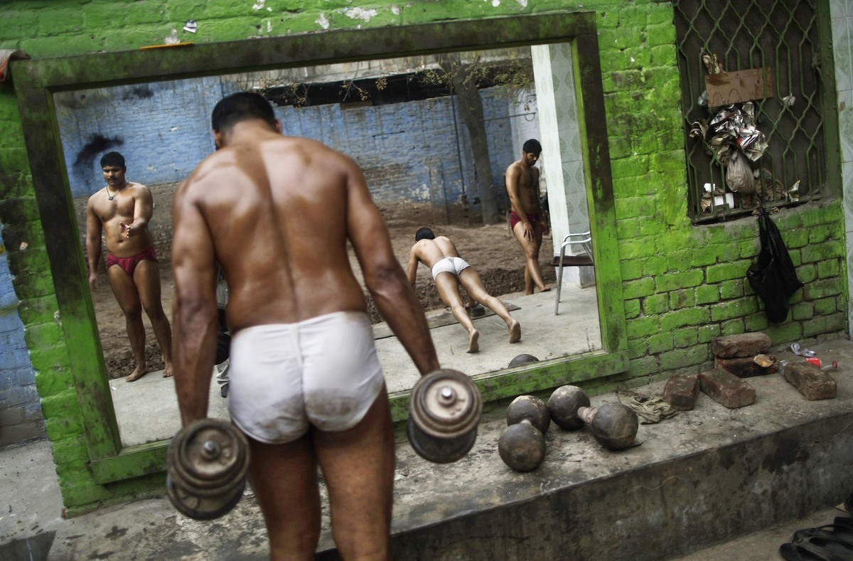 Pakistani Kushti wrestlers warm up before attending their daily training session, at a wrestling club in Lahore, Pakistan, Tu
