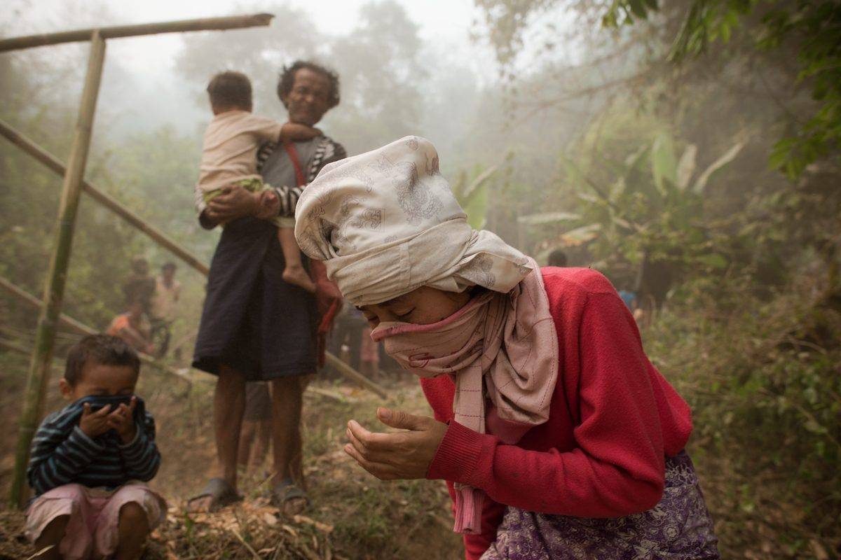 Myanmar refugees cover their mouths as a Thai army helicopter (not pictured) takes off at the Mae Surin camp in Mae Hong Son