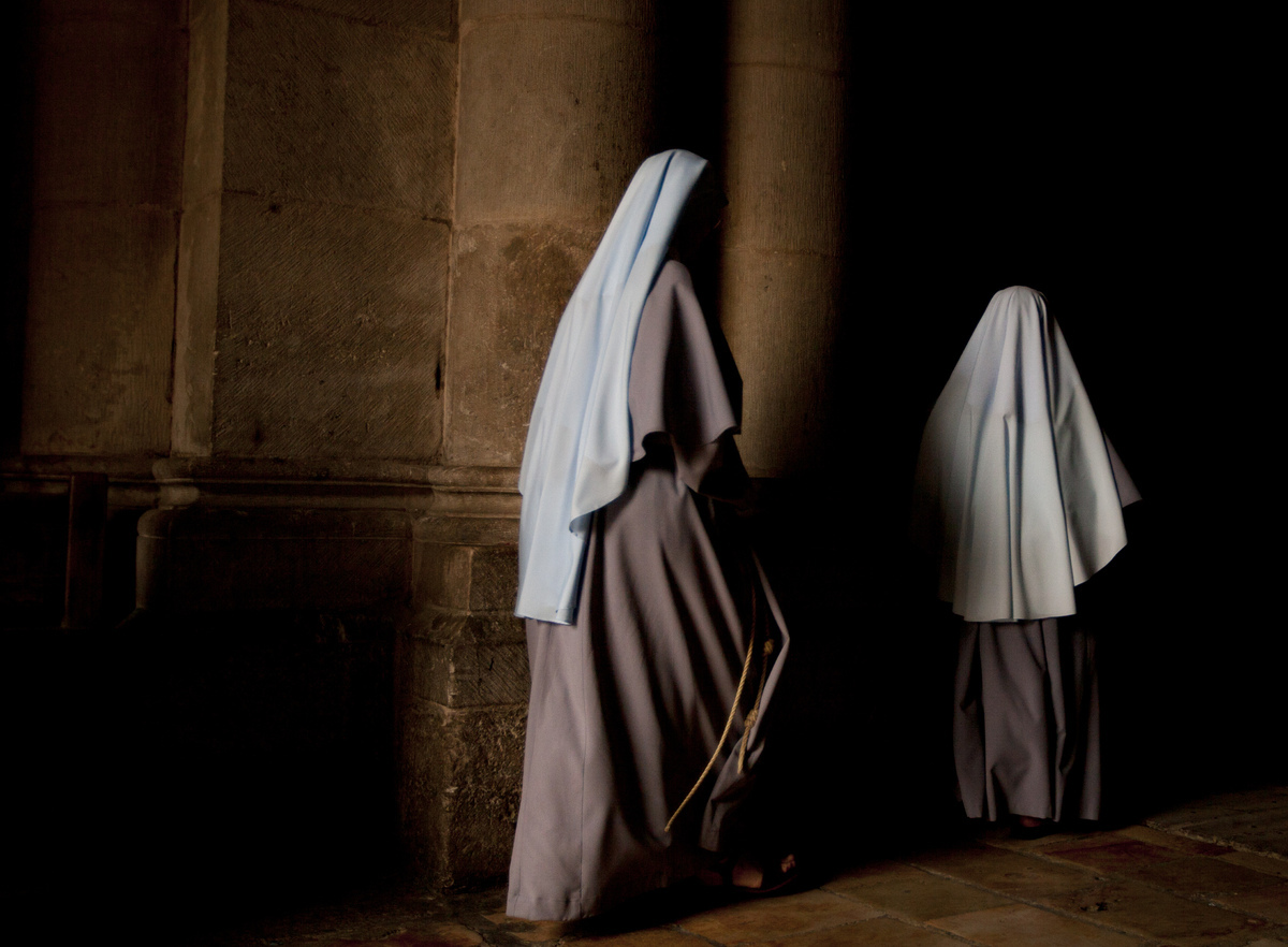 Nuns walk during the Sunday Easter mass at the Church of the Holy Sepulcher, traditionally believed to be the site of the cru