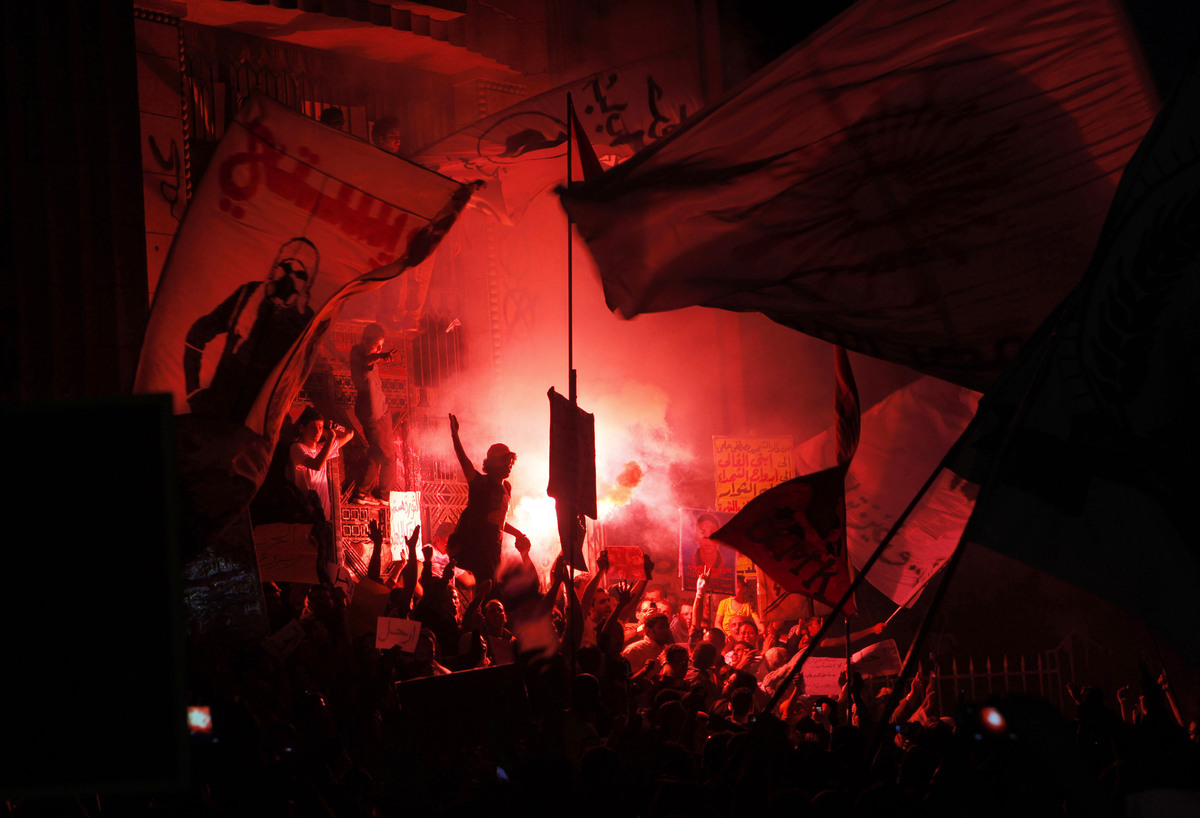 Members of Egypt's April 6 Youth Movement shout anti-Muslim Brotherhood slogans and light flares during a rally in front of t