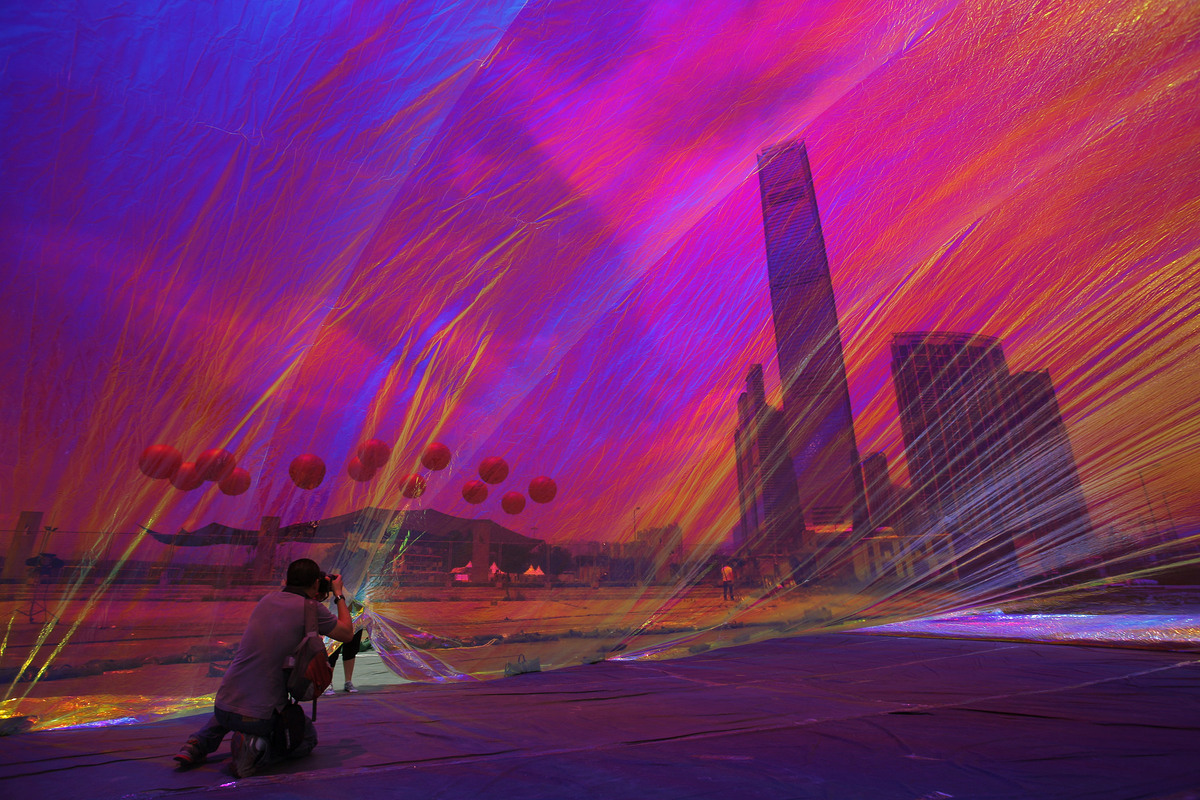 """Apartment towers and the International Commerce Centre, tower at center, are seen through a work of art entitled """"Poetic Cosm"""