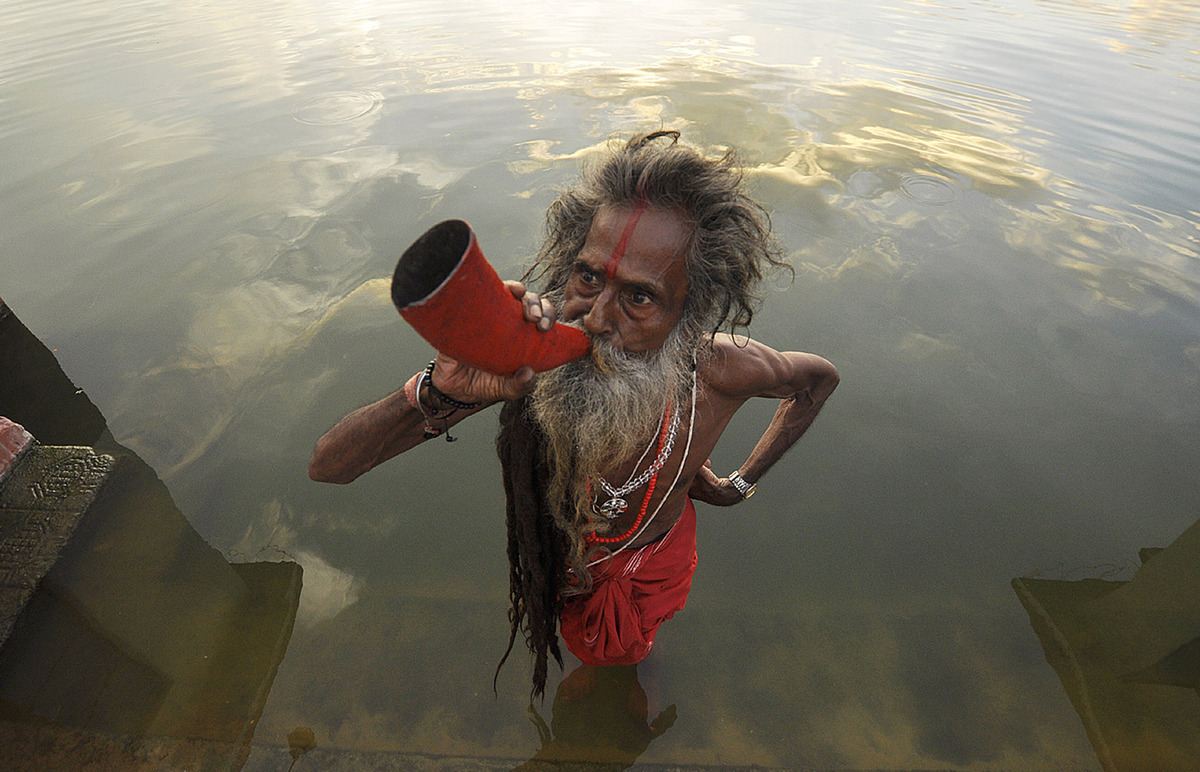 An Indian 'sadhu' - holy man' blows a buffalo horn on the eve of the traditional Kharchi Puja festival at Agartala, the capit