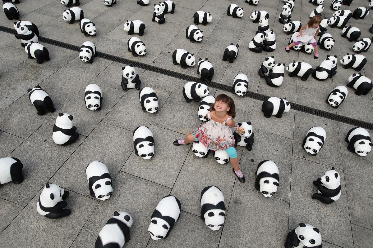 Elaia (C), 6, and her sister Lusitta, 4, play among 1,600 styrofoam panda bear sculptures displayed in front of Hauptbahnhof