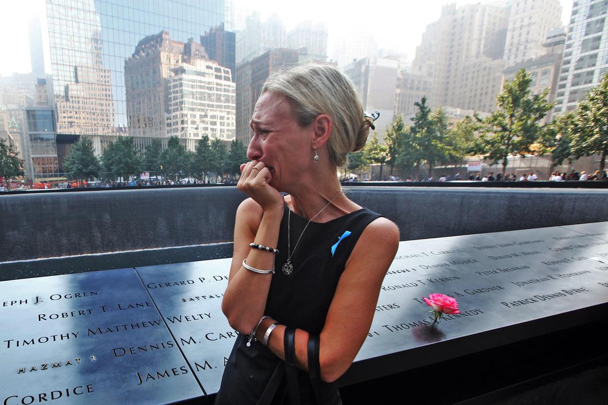 Carrie Bergonia of Pennsylvania looks over the name of her fiance, firefighter Joseph Ogren at the 9/11 Memorial during cerem