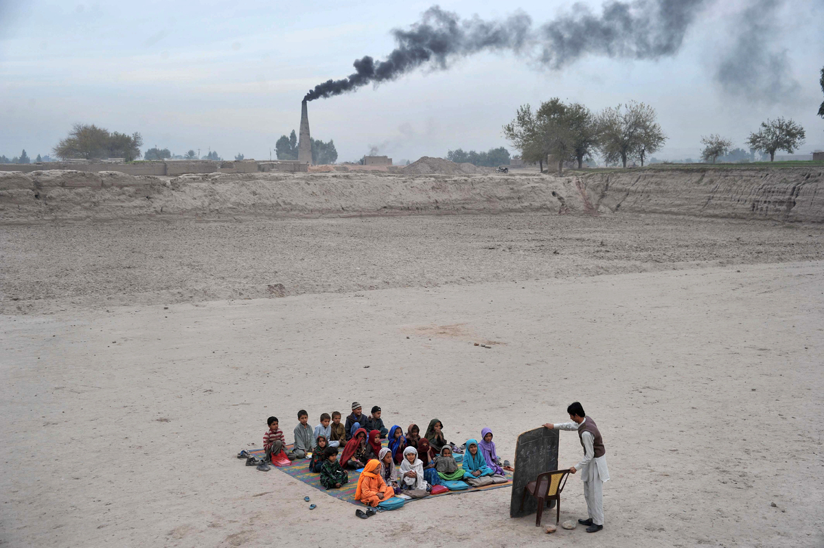 Afghan schoolchildren take lessons in an open classroom at a refugee camp on the outskirts of Jalalabad, Nangarhar province o