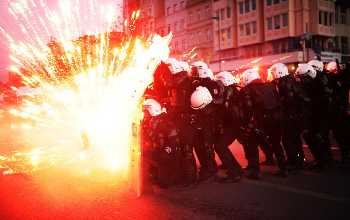 Turkish riot police officers take cover as Kurdish protesters shoot fireworks at them during clashes in central Istanbul on D