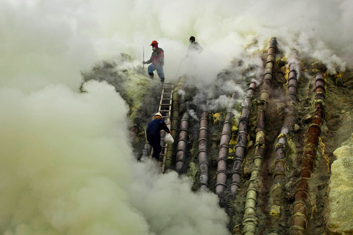 A sulfur miner carries a goats head in a white bag as he climbs to bury the head in the crater as part of an annual offering