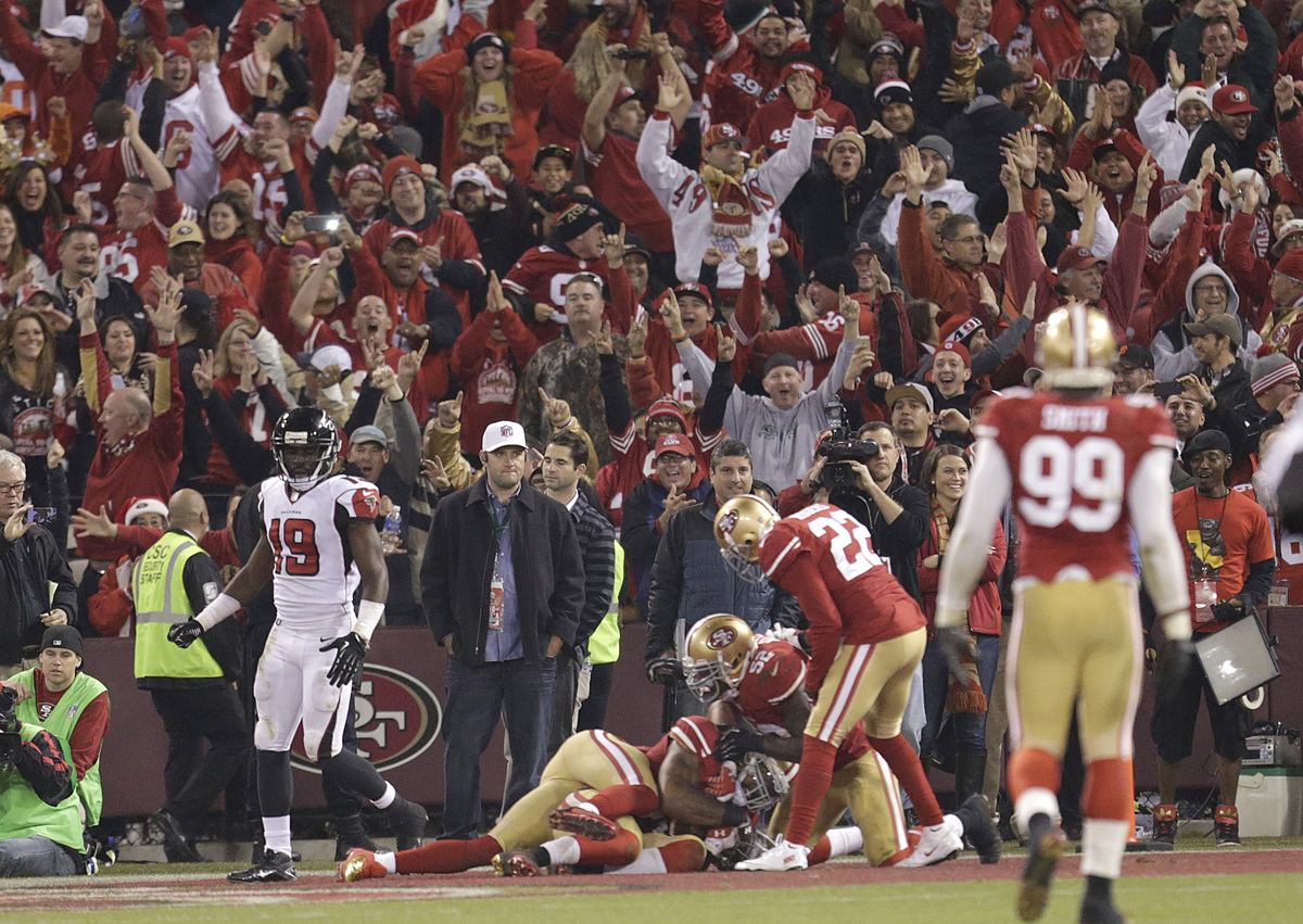 Fans celebrate after San Francisco 49ers linebacker NaVorro Bowman, bottom, returned an interception 89 yards for a touchdown