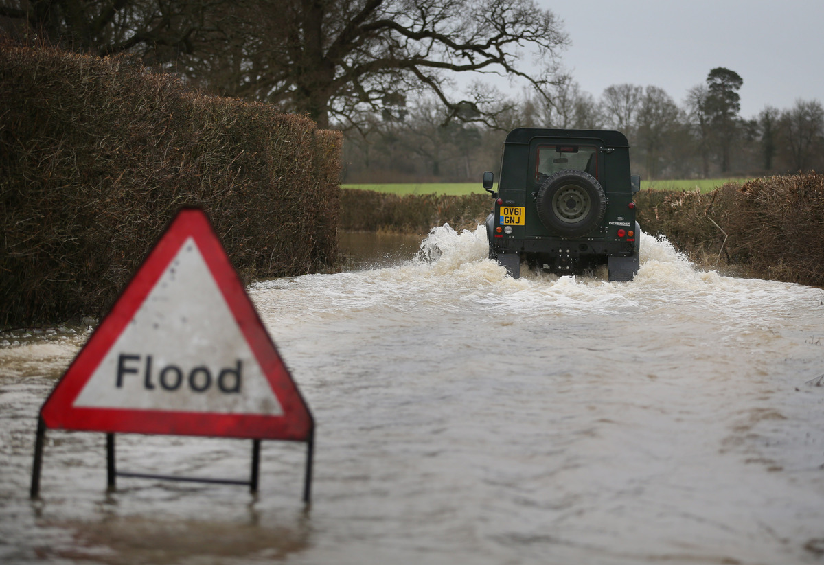 LINGFIELD, UNITED KINGDOM - DECEMBER 27: A Landrover makes it's way along a flooded road near Lingfield on December 27, 2013