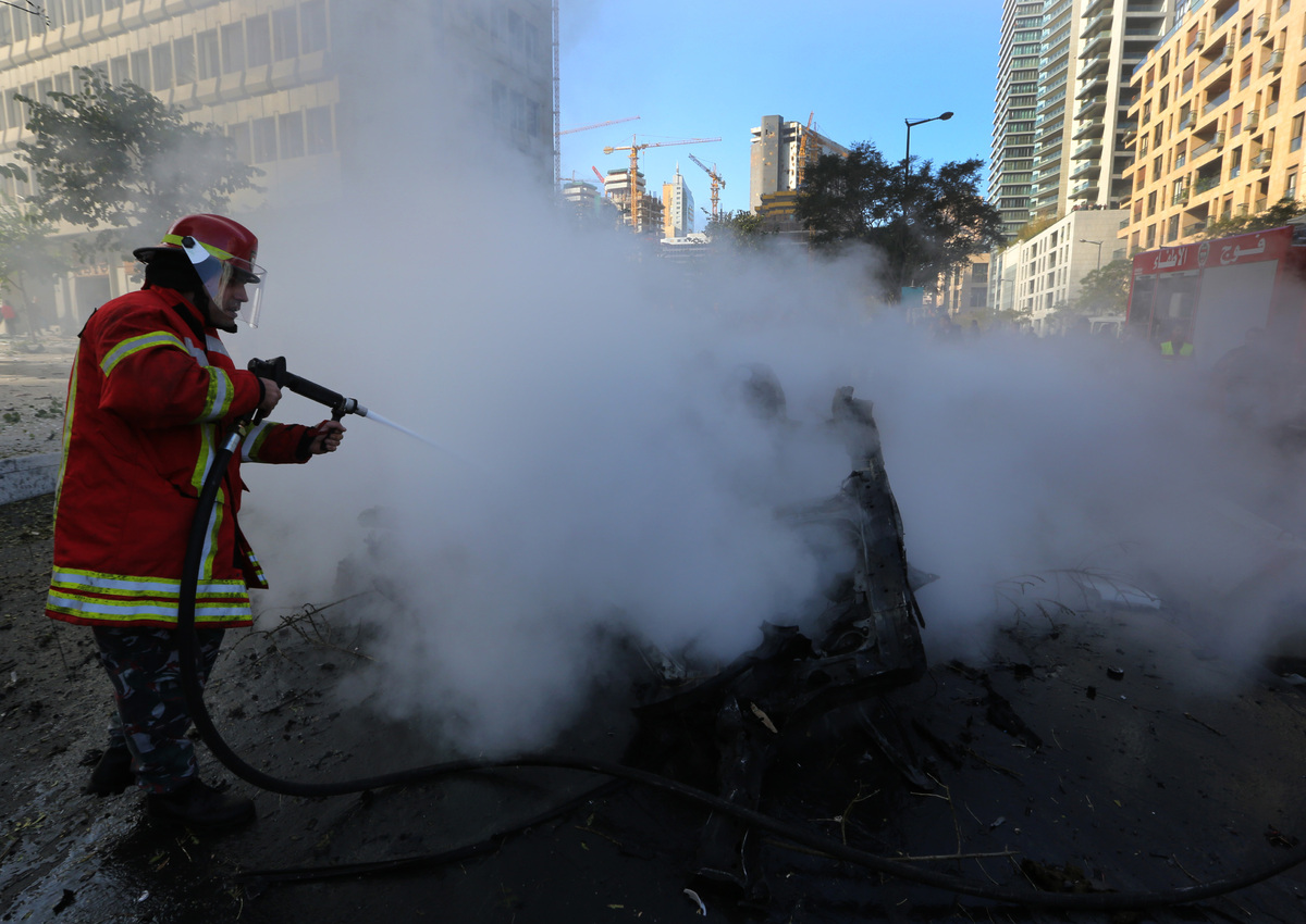 A Lebanese firefighter extinguishes burned vehicles at the scene of an explosion in Beirut, Lebanon, Friday, Dec. 27, 2013. (