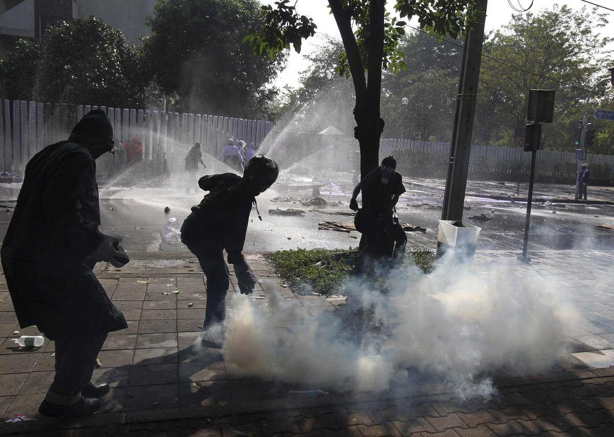 An anti-government protester, second from left, prepares to throw back a tear gas canister fired by riot police near a sport