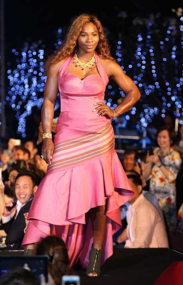 US tennis player Serena Williams presents a silk dress creation on the catwalk during a fashion show at the International Hot