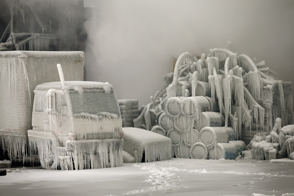 A truck is covered in ice as firefighters help to extinguish a massive blaze at a vacant warehouse on January 23, 2013 in Chi