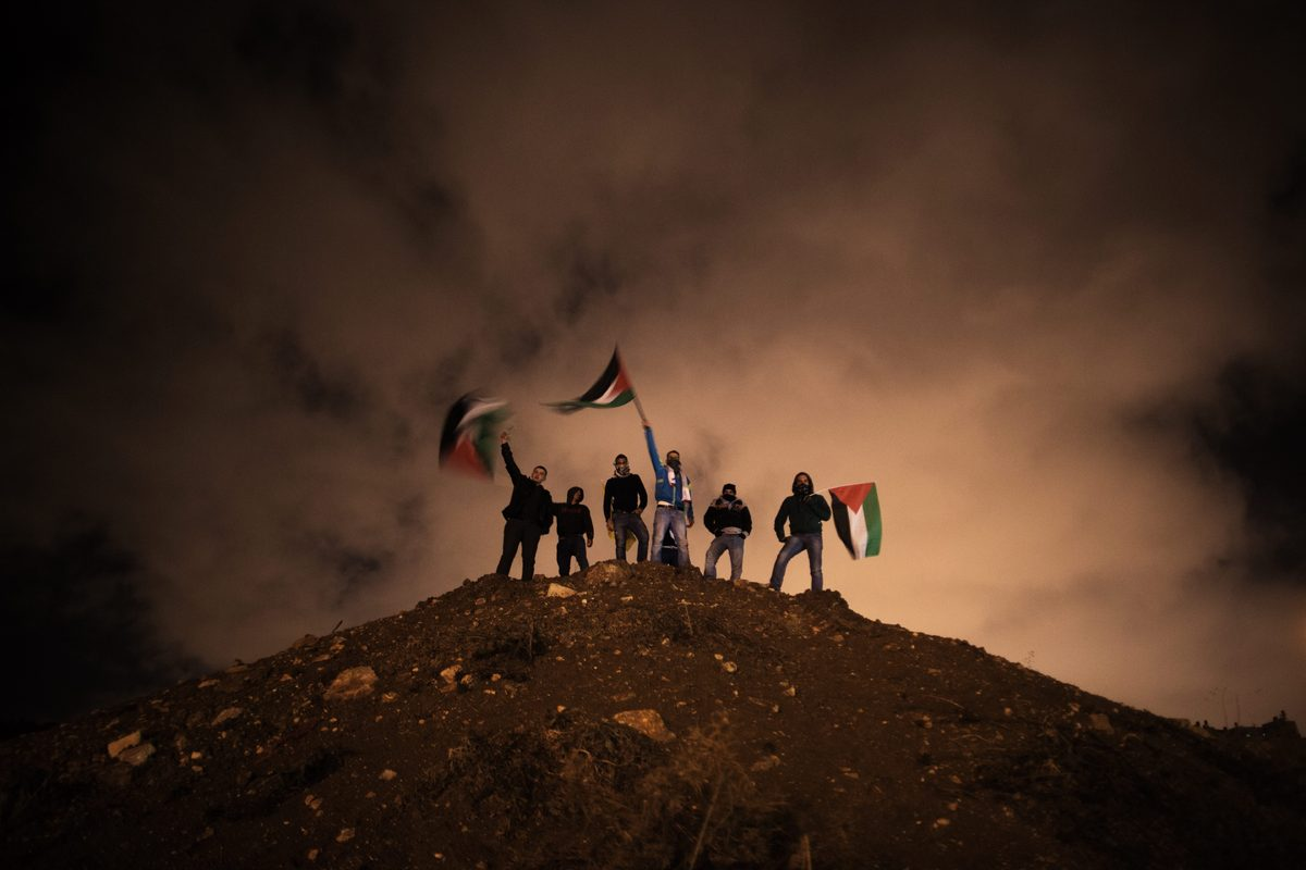 Palestinians wave their national flag as they await the release of Palestinian prisoners to Jerusalem December 31, 2013.  Isr