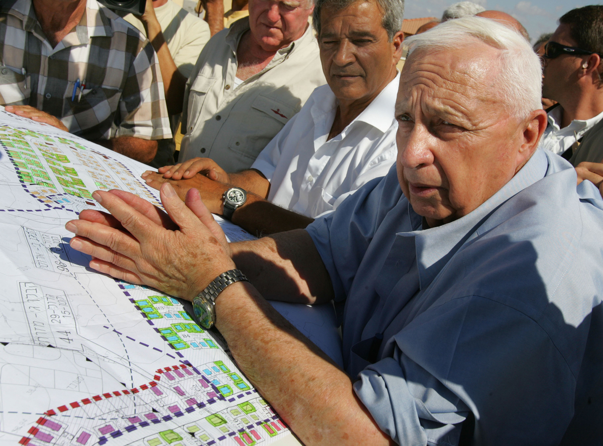 Israeli Prime Minister Ariel Sharon leans over housing plans as he meets with contractors who are building temporary housing