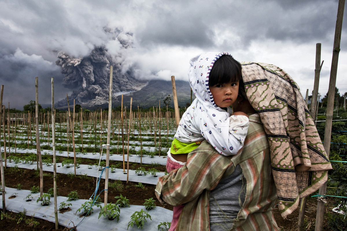 A woman carries her daughter in a nearby field as Mount Sinabung spews pyroclastic smoke on January 4, 2014 in Karo District,