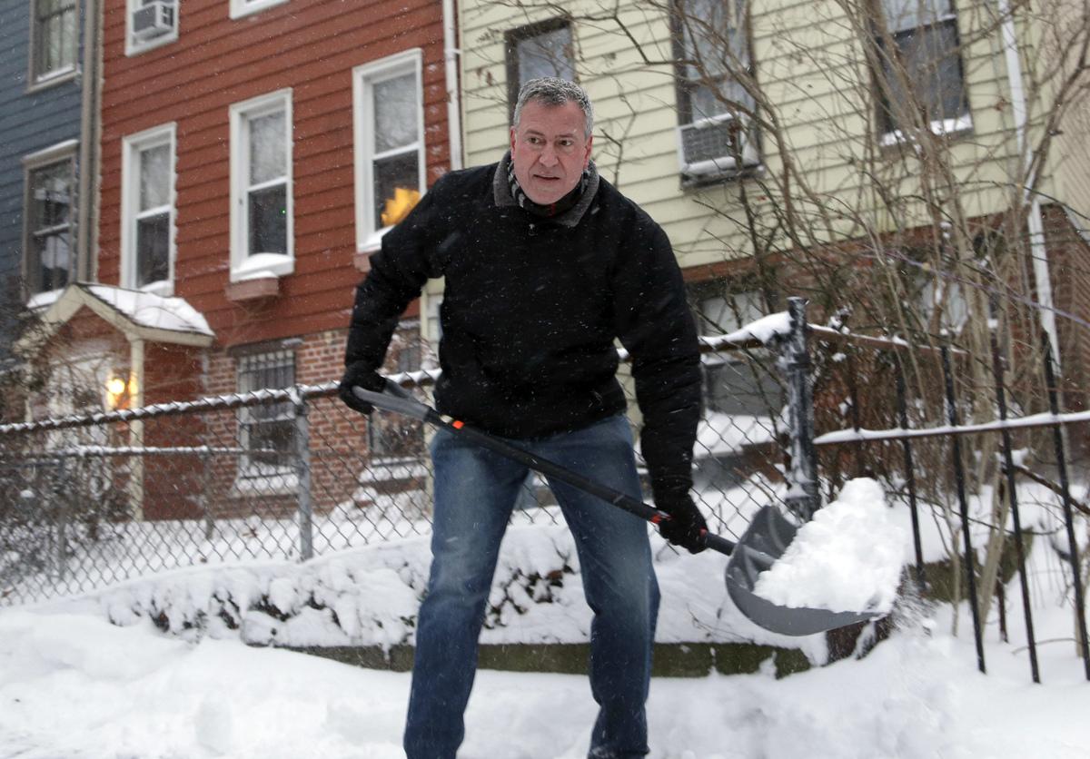 New York City Mayor Bill de Blasio shovels the sidewalk in front of his house in New York, Friday, Jan. 3, 2014. New York Cit