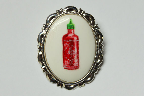 "<em><a href=""https://www.etsy.com/listing/170914020/hand-painted-cock-sauce-brooch-sriracha?ref=sr_gallery_40&ga_search_query"