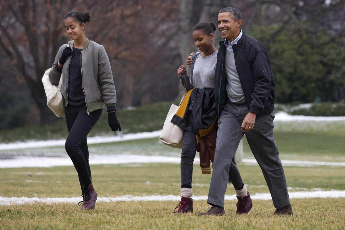President Barack Obama, right, hugs his daughter Sasha as they and Malia, left, return to the White House from their fifteen-