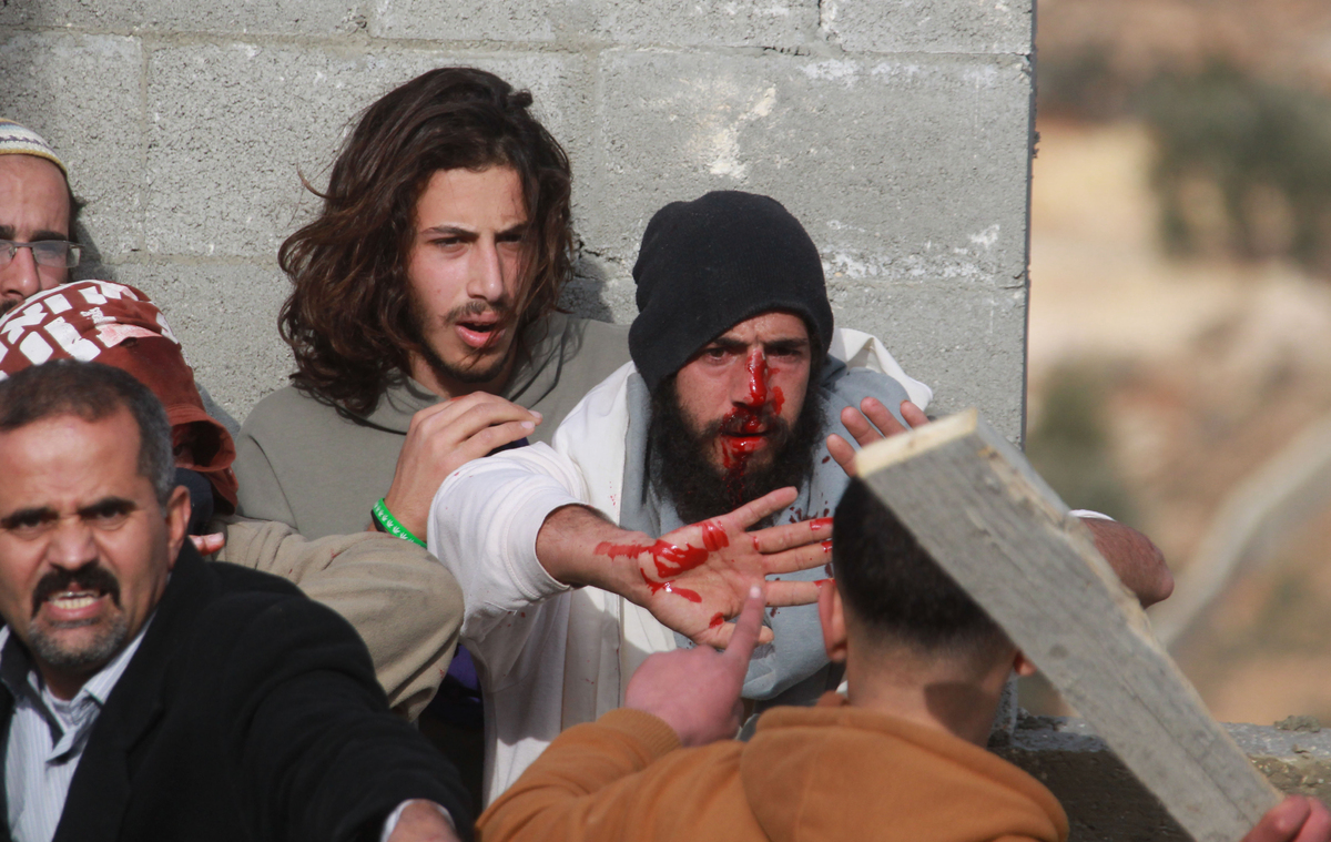 A Palestinian man (L) tries to prevent a fellow Palestinian from the village of Qusra (front) from beating a group of Israeli