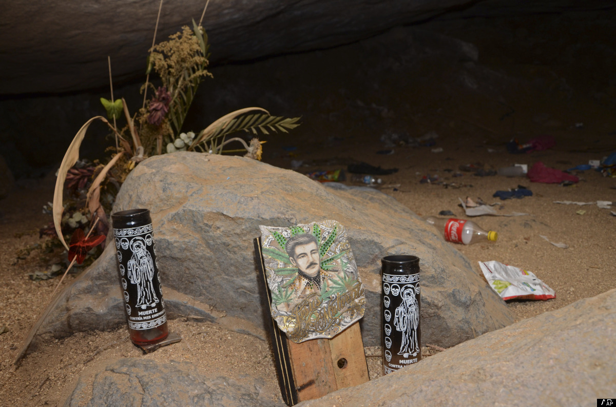 A stone with candles depicting the Santa Muerte and and image of Jesus Malverde, stand at the entrance to a cave near where