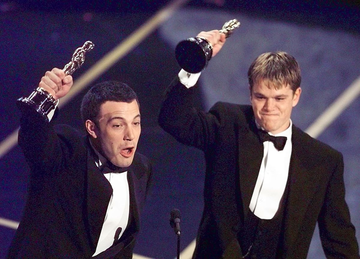 LOS ANGELES, UNITED STATES:  Ben Affleck (L) and Matt Damon hold up their Oscars after winning in the Original Screenplay  Ca